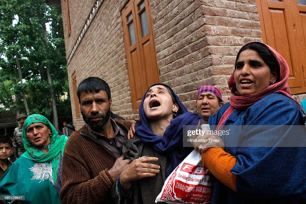 Kashmiri women try to comfort a wailing wife of an Army soldier Mushtaq Ahmad Mir during the funeral procession at Qazipora Chadoora district, on May 20, 2014 in Srinagar, India. Mushtaq Ahmad Mir, an Army soldier who was killed in an encounter at Chadoora yesterday. An Army soldier was killed and three others injured in an ongoing encounter at Chadoora in district Budgam of central Kashmir. Sources said that militants managed their escape from the spot and forces were now extending the cordon to more areas.