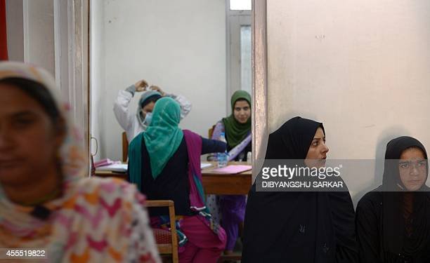 Kashmiri women wait for their appointment with a woman gynaecologist at the outdoor unit of the Government Maternity Hospital in Srinagar on...