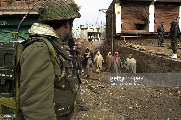 Kashmiri women walk between Indian army soldiers after an explosion damaged a bus in Lawaypora some 10kms north of Srinagar 30 December 2003 At least...