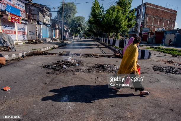 Kashmiri women walk in front a smoldering barricade left by Kashmiri protesters in the Habba Kadal after a protest against revocation of Article 370...