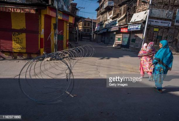Kashmiri women walk past a razor wire cordon as they negotiate curfew like restrictions in the Habba Kadal on August 18, 2019 in Srinagar, the summer...