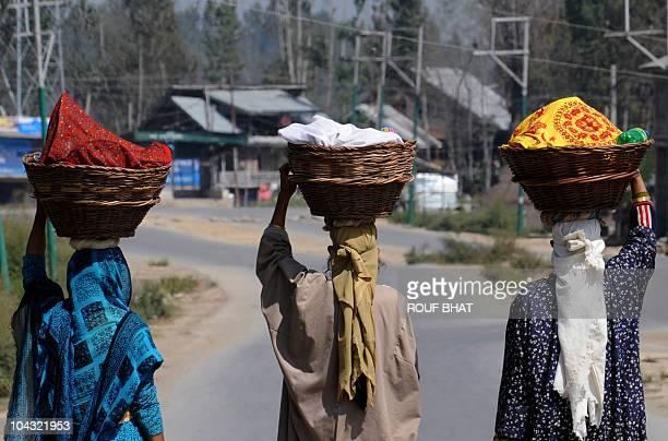 Kashmiri women walk through curfewbound Tangmarg village north of Srinagar on September 21 2010 Indian lawmakers visiting Kashmir cut short a...