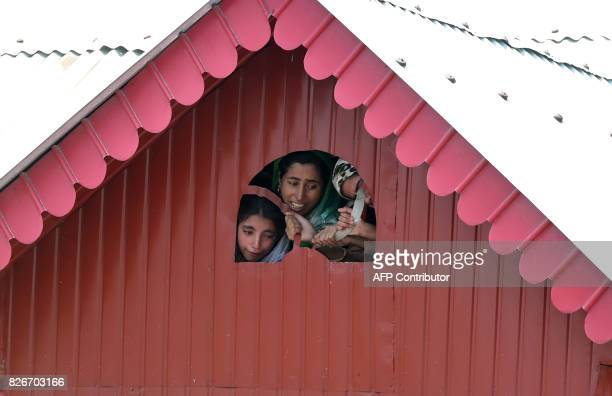 Kashmiri women watch the funeral procession of slain rebel Abid Ahmed during his funeral procession in the village of Hajinar in the district...