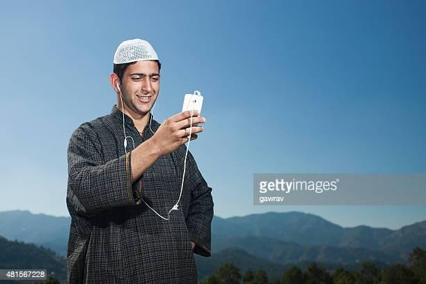 Kashmiri jeune homme dans les montagnes à un téléphone avec casque sur les oreilles.