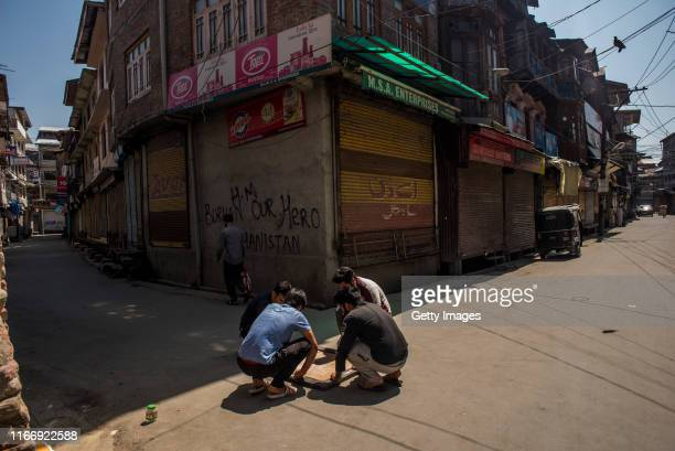 Kashmiri young men play a carom board game in middle of the road in the closed commercial hub of the city center during curfew like restrictions on...