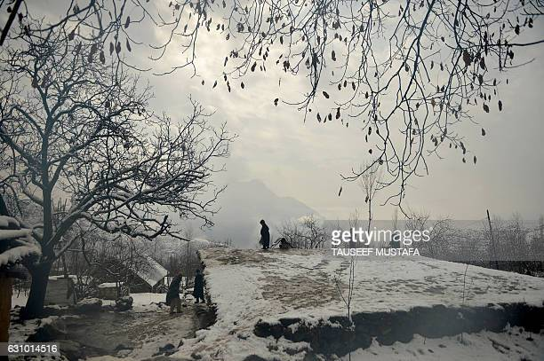 Kashmiri youth clears snow off the top of a mud house on the outskirts of Srinagar on January 5 2017 The subzero temperatures has frozen many water...