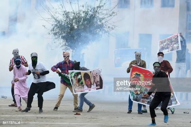 Kashmiri youth hold banners and throw stones during clashes between protesters and Indian government forces in downtown Srinagar on September 2 2017...