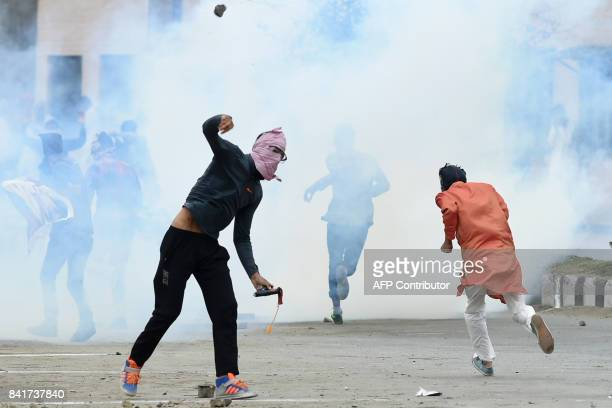 A Kashmiri youth throws a stone during clashes between protesters and Indian government forces in downtown Srinagar on September 2 2017 Clashes broke...