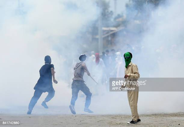A Kashmiri youth throws stones as others run away during clashes between protestors and Indian government forces in Srinagar on September 2 2017...