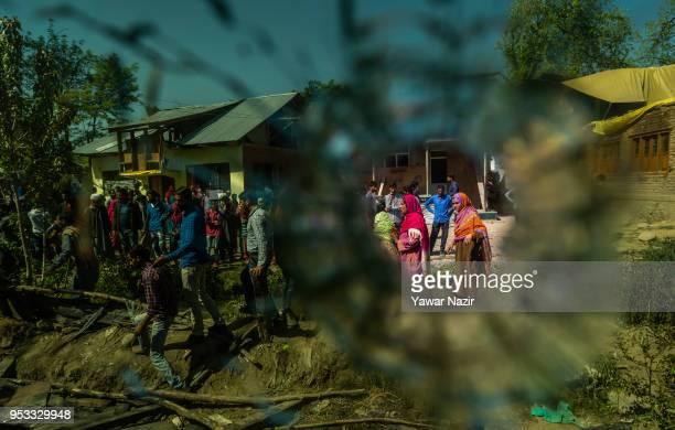 Kashmiris are seen through a bullet hole at a residential house destroyed yesterday in a gun battle between Indian armed forces and Kashmiri rebels...