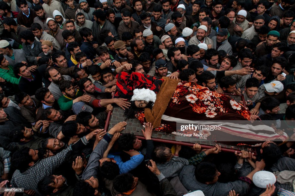 Kashmiris attend the funeral procession of one of three Kashmir militants that were killed in a gun battle with Indian government forceson April 26, 2014 in Drobgam, 55 km (34 miles) south of Srinagar, the summer capital of Indian administered Kashmir, India. Thousands of Kashmiri Muslims attended the funeral procession of three Kashmiri militants killed on Saturday during a gun battle with Indian government forces. The militants were holed up in a residential house in Shupian and killed after an overnight gun battle with forces, in which an Indian army major and a trooper were also killed after one of the militants hiding in the debris fired indiscriminately,police said.