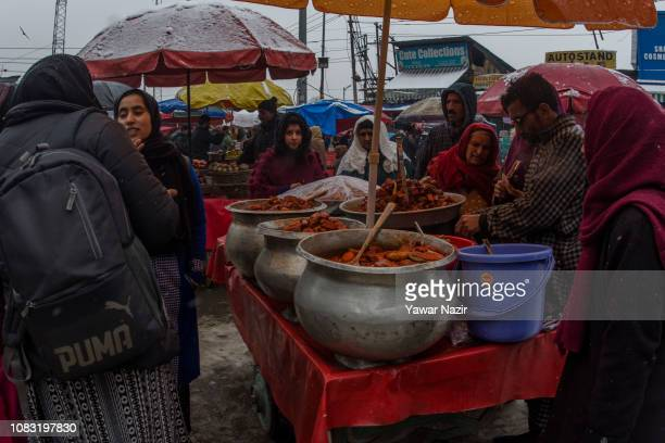 Kashmiris buy pickle from a vendor sells amid fresh snowfall on January 16 2019 in Srinagar the summer capital of Indian administered Kashmir India...