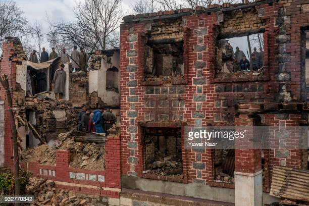 Kashmiris gather around the war ravaged residential houses after a gun battle between Indian government forces and Kashmiri rebels on March 16 2018...