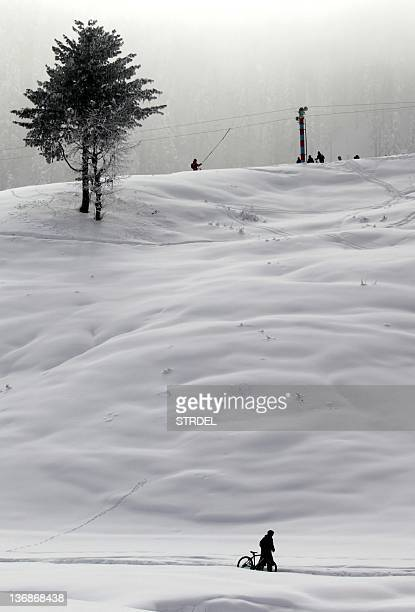 A Kashmiris man pushes his bicycle on a snow covered road as people use a ski lift in the background at Kashmir's ski resort Gulmarg 54 km west of...