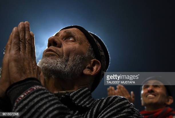 TOPSHOT Kashmiris offer prayers as a priest displays a relic at the shrine of Sheikh Abdul Qadir Geelani in Srinagar on January 5 2018 Devotees are...