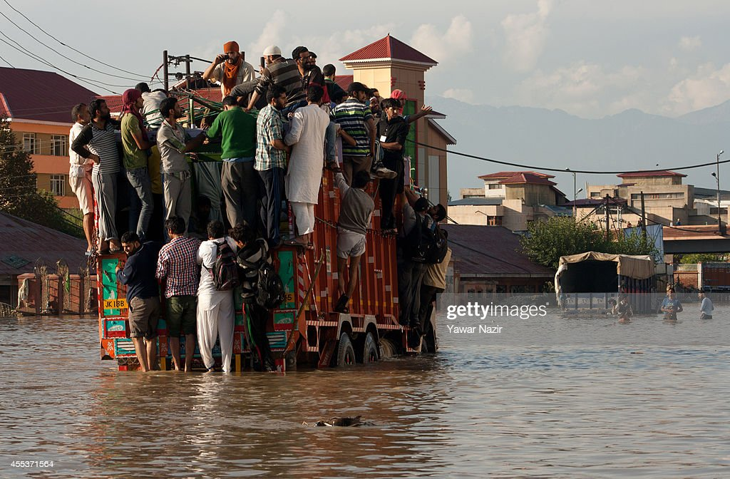 Kashmiris on top of a truck try to cross a submerged road in the flooded main city on September 13, 2014 in Srinagar, the summer capital of Indian administered Kashmir, India. More than a million people have been cut off from clean water and thousands of buildings, even hospitals submerged in flood water have been left uninhabitable. The floods in the Himalayan region of Kashmir are believed to be the worst in decades and have left approximately 400,000 people stranded and over 200 dead.