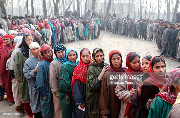 Kashmiris stand in queue to cast their votes outside a polling station during the first phase of voting to the Jammu and Kashmir state assembly...