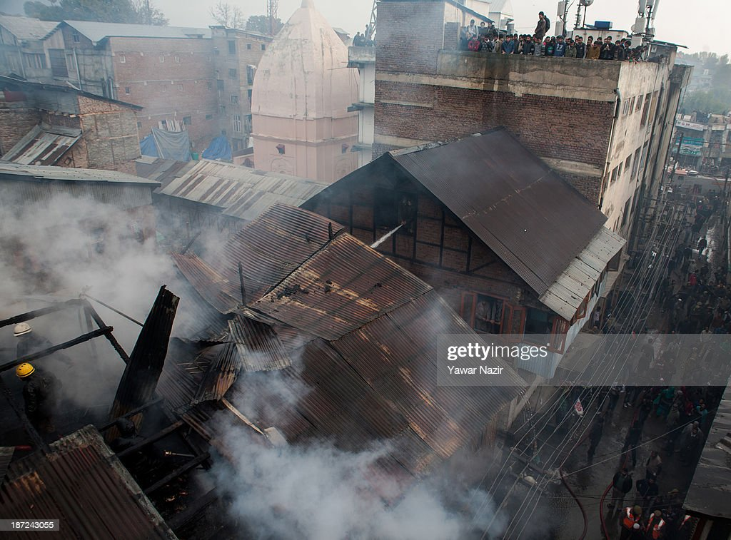 Kashmiris watch firefighters extinguishing a fire that gutted residential houses on November 07, 2013, in Srinagar the summer capital of Indian administered Kashmir, India. Several families were left homeless in Maharaja Bazar locality in uptown Srinagar and no injuries were reported.