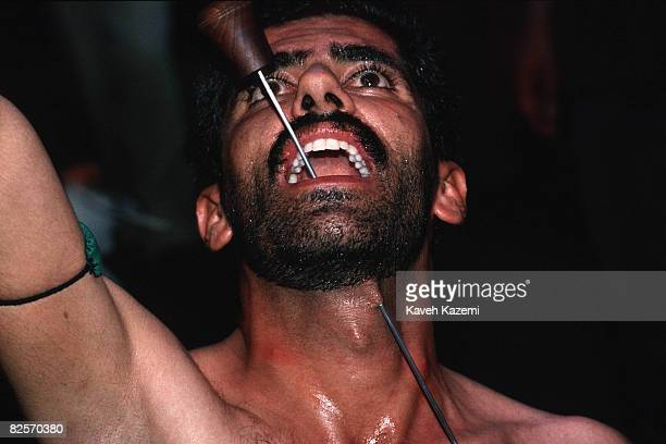 A Kasnazani dervish pierces his lower jaw and throat with a skewer whilst in trance during a remembrance ceremony in Sanandaj capital of the...