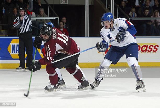 Kaspars Daugavins of Team Latvia skates the puck away from Erik Piatak of Team Slovakia during their World Junior Hockey Championship game at...