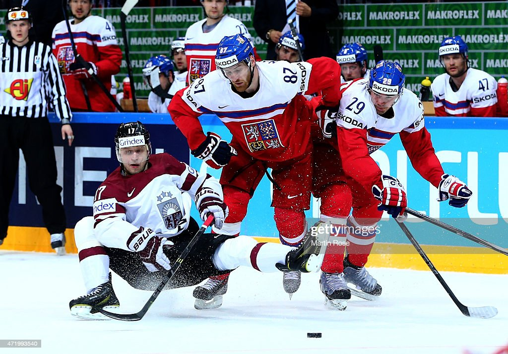 Kaspars Saulietis (L) of Latvia and Jakub Nakladal (C) and Jan Kolar of Czech Republic battle for the puck during the IIHF World Championship group A match between Latvia and Czech Republic at o2 Arenaon May 2, 2015 in Prague, Czech Republic.