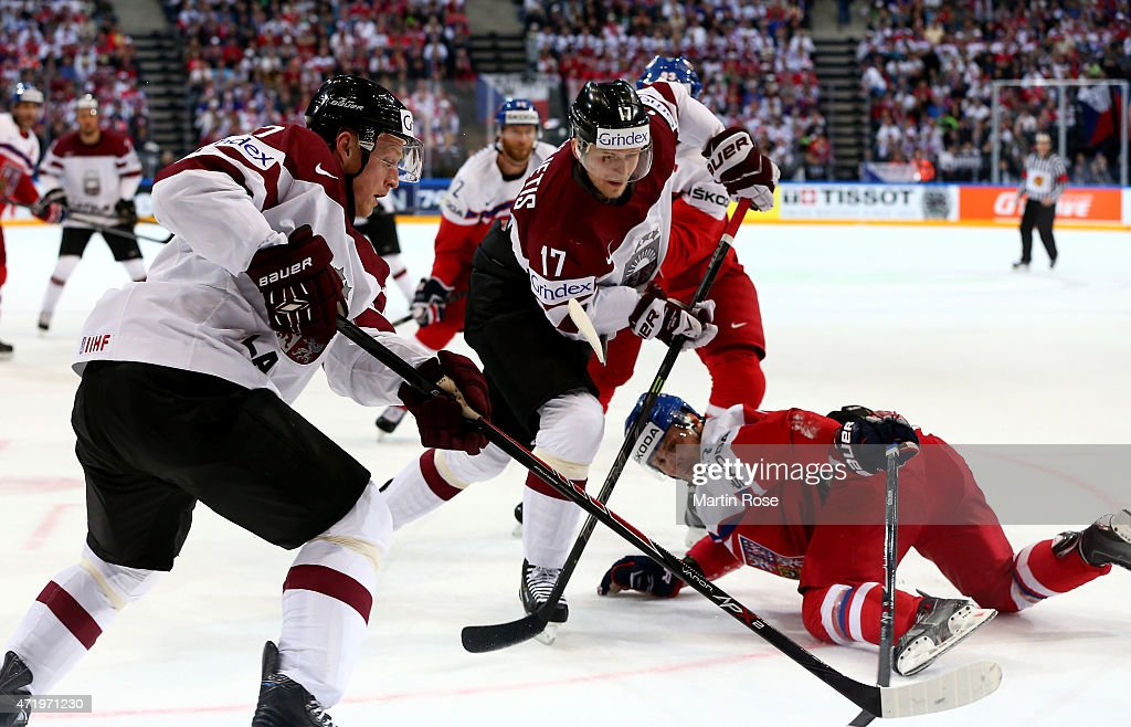 Kaspars Saulietis (C) of Latvia and Ondrej Nemec (R) of Czech Republic battle for the puck during the IIHF World Championship group A match between Latvia and Czech Republic at o2 Arenaon May 2, 2015 in Prague, Czech Republic.