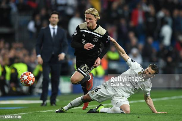Kasper Dolberg of Ajax competes for the ball with Nacho of Real Madrid CF during the UEFA Champions League Round of 16 Second Leg match between Real...