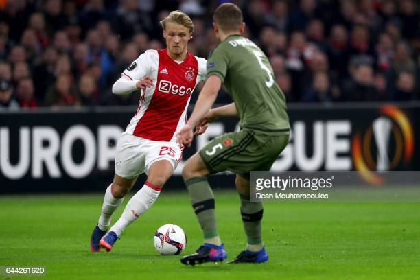 Kasper Dolberg of Ajax is faced by Maciej Dabrowski of Legia Warszawa during the UEFA Europa League Round of 32 second leg match between Ajax...