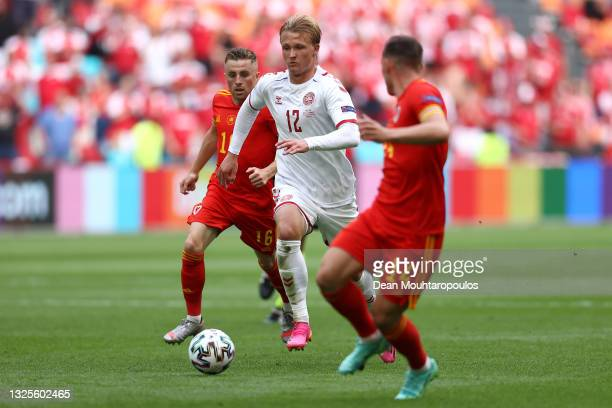 Kasper Dolberg of Denmark runs with the ball whilst under pressure from Joe Morrell of Wales during the UEFA Euro 2020 Championship Round of 16 match...