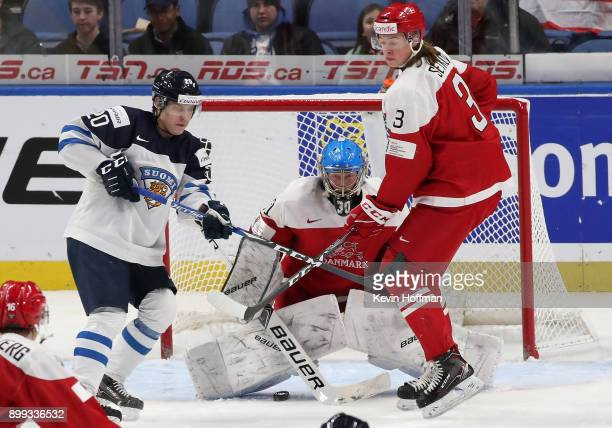 Kasper Krog of Denmark makes the save against as Eeli Tolvanen of Finland looks for a rebound in the third period during the IIHF World Junior...