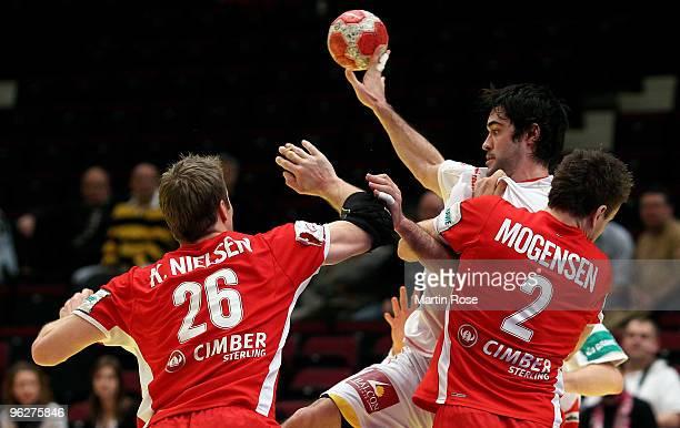 Kasper Nielsen and Thomas Mogensen of Denmark try to block Raul Entrerrios of Spain during the Men's Handball European qualifyer place 5 match...