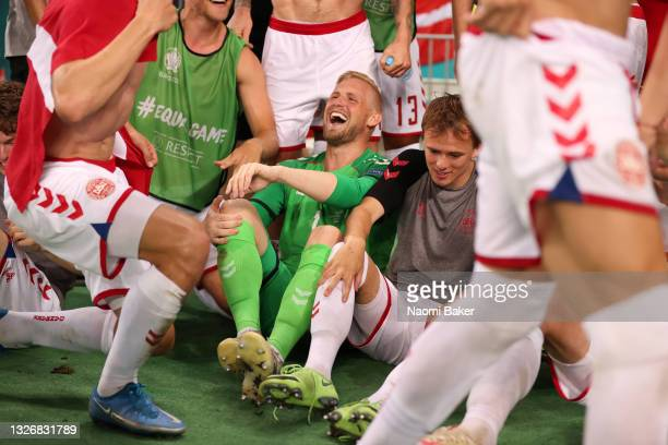 Kasper Schmeichel and Mikkel Damsgaard of Denmark celebrate with teammates after victory in the UEFA Euro 2020 Championship Quarter-final match...
