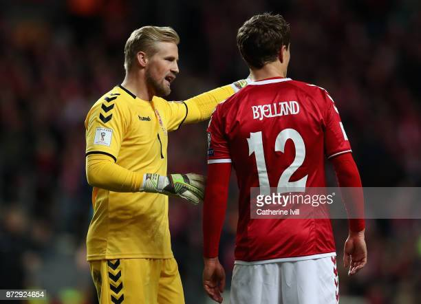 Kasper Schmeichel of Denmark and Andreas Bjelland of Denmark speak during the FIFA 2018 World Cup Qualifier PlayOff First Leg between Denmark and...