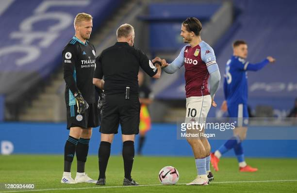Kasper Schmeichel of Leicester City and Jack Grealish of Aston Villa take part in the coin toss with referee Jonathan Moss prior to the Premier...