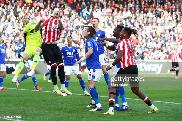 Kasper Schmeichel of Leicester City catches Pontus Jansson of Brentford with his glove during the Premier League match between Brentford and...
