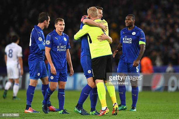 Kasper Schmeichel of Leicester City celebrates his team's win with his team mate Robert Huth in the UEFA Champions League Group G match between...