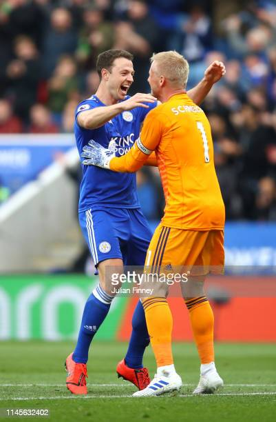 Kasper Schmeichel of Leicester City celebrates with Jonny Evans as he assists a goal for Jamie Vardy during the Premier League match between...