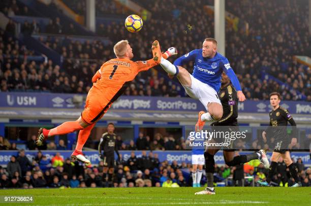 Kasper Schmeichel of Leicester City dives to save from Wayne Rooney of Everton during the Premier League match between Everton and Leicester City at...