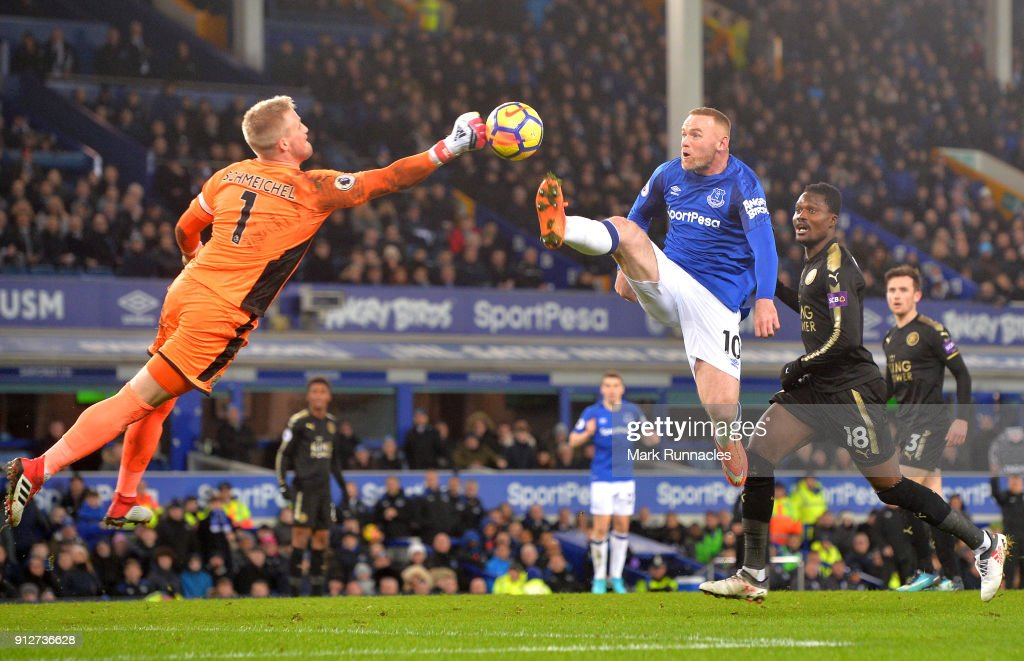 Kasper Schmeichel of Leicester City dives to save from Wayne Rooney of Everton during the Premier League match between Everton and Leicester City at Goodison Park on January 31, 2018 in Liverpool, England.
