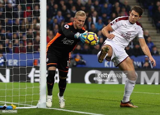 Kasper Schmeichel of Leicester City is challenged by James Tarkowski of Burnley during the Premier League match between Leicester City and Burnley at...