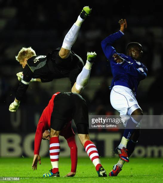 Kasper Schmeichel of Leicester City is taken out by Greg Cunningham of Nottingham Forest during the npower championship match between Leicester City...