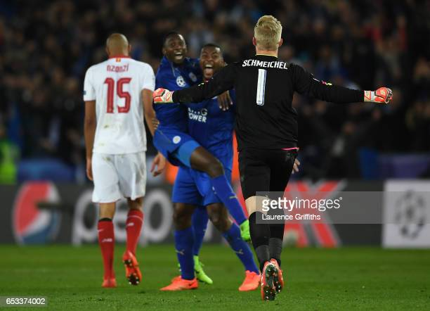 Kasper Schmeichel of Leicester City runs to celebrate with teammates Wilfred Ndidi and Wes Morgan of Leicester City as the final whistle blows during...
