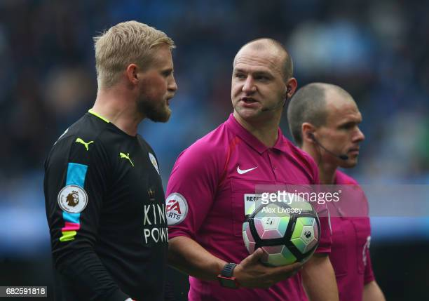 Kasper Schmeichel of Leicester City speaks to referee Bobby Madley as they walk off at half time during the Premier League match between Manchester...