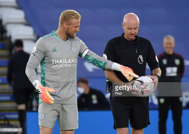 Kasper Schmeichel of Leicester City speaks with referee Lee Mason about the match ball during the Premier League match between Leicester City and...