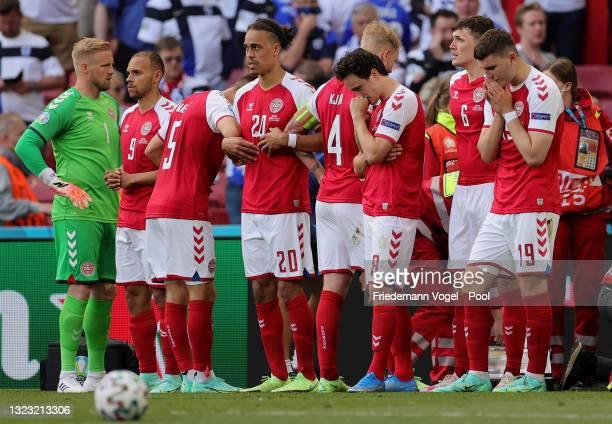 Kasper Schmeichel, Yussuf Poulsen, Thomas Delaney and Jonas Wind of Denmark look dejected as they surround Christian Eriksen of Denmark as he...