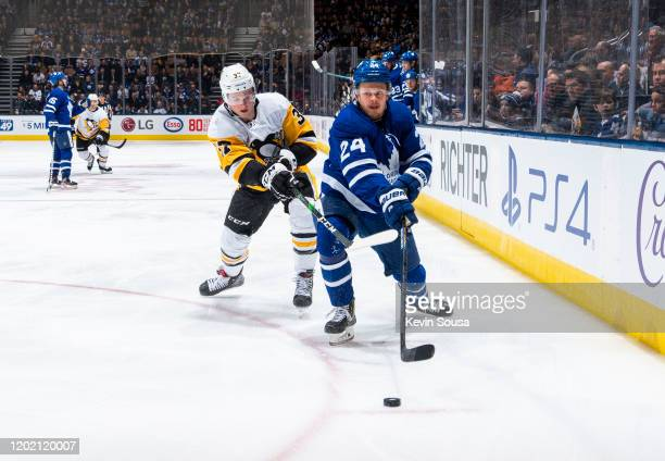 Kasperi Kapanen of the Toronto Maple Leafs battles for the puck against Sam Lafferty of the Pittsburgh Penguins during the first period at the...