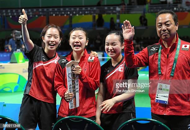 Kasumi Ishikawa Ai Fukuhara Mima Ito and head coach Yasukazu Murakami of Japan celebrate winning the bronze medals after beating Singapore in the...