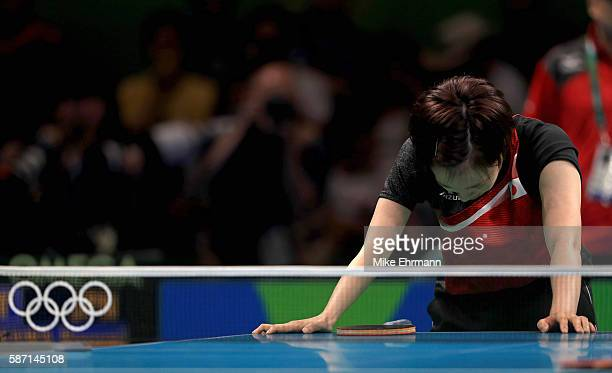 Kasumi Ishikawa of Japan fights of cramps during a Women's Singles third round match against Song I Kim of the Peoples Republic of Korea on Day 2 of...