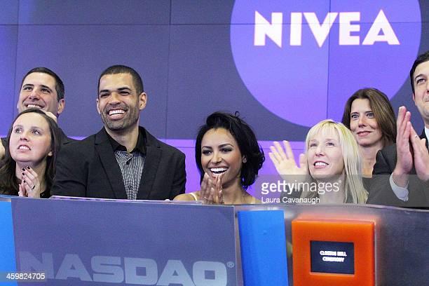 Kat Graham and Cottrell Guidry ring the closing bell at NASDAQ MarketSite on December 31 2013 in New York City