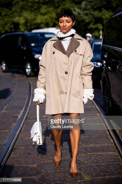 Kat Graham, wearing a long beige jacket, brown heels and white Tod's bag, is seen outside the Tod's show during Milan Fashion Week Spring/Summer 2020...